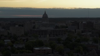 DX0002_162_005 - 5.7K stock footage aerial video reveal smoke stacks while flying away from the capitol dome at sunset, Madison, Wisconsin
