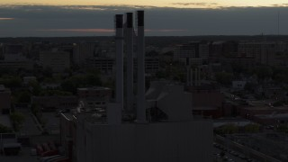 DX0002_162_010 - 5.7K stock footage aerial video of approach and orbit power plant smoke stacks at twilight, Madison, Wisconsin