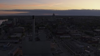 DX0002_162_017 - 5.7K stock footage aerial video the capitol dome seen while passing power plant smoke stacks at twilight, Madison, Wisconsin