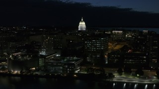 DX0002_162_029 - 5.7K stock footage aerial video ascend away from capitol dome and downtown buildings at twilight, Madison, Wisconsin