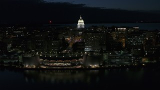 DX0002_162_030 - 5.7K stock footage aerial video focus on capitol dome while passing the convention center at night, Madison, Wisconsin