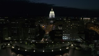 DX0002_162_034 - 5.7K stock footage aerial video passing downtown buildings while focused on the capitol at night, Madison, Wisconsin
