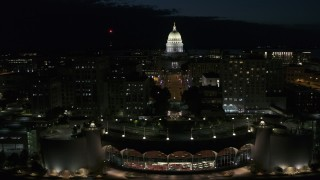 DX0002_162_036 - 5.7K stock footage aerial video flyby convention center while focused on the capitol at night, Madison, Wisconsin