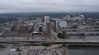 DX0002_164_002 - 5.7K stock footage aerial video flyby and away from an apartment high-rise and office buildings near bridges and river, Downtown Cedar Rapids, Iowa