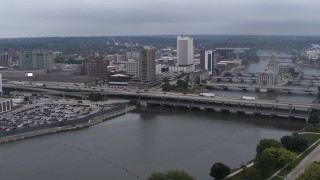 DX0002_164_012 - 5.7K stock footage aerial video fly toward apartment high-rise and bridges spanning the river, Downtown Cedar Rapids, Iowa