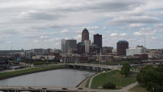 DX0002_165_018 - 5.7K stock footage aerial video ascend from park for view of skyline across the river, Downtown Des Moines, Iowa