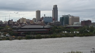 DX0002_169_021 - 5.7K stock footage aerial video descend by river and riverfront park with view of skyline, Downtown Omaha, Nebraska
