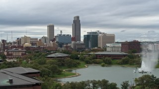DX0002_169_024 - 5.7K stock footage aerial video reverse view of a fountain in a park and skyline, Downtown Omaha, Nebraska