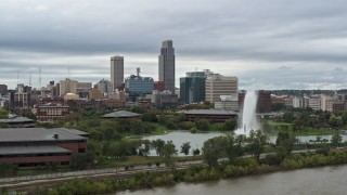 DX0002_169_026 - 5.7K stock footage aerial video flying by a fountain in a park and skyline, Downtown Omaha, Nebraska