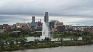 DX0002_169_027 - 5.7K stock footage aerial video passing by a fountain in a park and skyline, Downtown Omaha, Nebraska