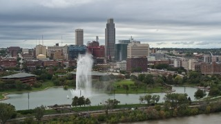 DX0002_169_030 - 5.7K stock footage aerial video of the city's skyline while flying by a park fountain, Downtown Omaha, Nebraska