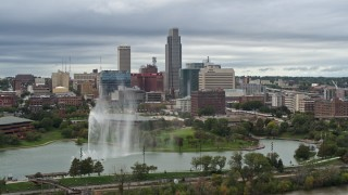 DX0002_169_031 - 5.7K stock footage aerial video of the city's skyline while passing a park fountain, Downtown Omaha, Nebraska