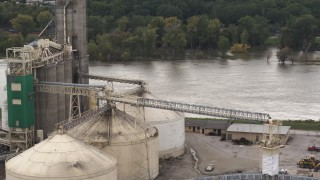 DX0002_170_007 - 5.7K stock footage aerial video orbit storage tanks and grain elevator by river, Council Bluffs, Iowa