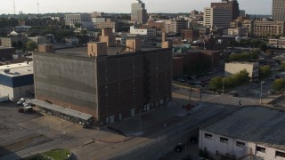 DX0002_170_047 - 5.7K stock footage aerial video of a stationary view of a brick office building at sunset, Downtown Omaha, Nebraska