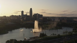 DX0002_172_008 - 5.7K stock footage aerial video ascending away from a fountain with view of skyline at sunset, Downtown Omaha, Nebraska