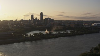 DX0002_172_009 - 5.7K stock footage aerial video flying away from a fountain with view of skyline at sunset, Downtown Omaha, Nebraska