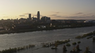 DX0002_172_010 - 5.7K stock footage aerial video descend by river with view of a fountain and skyline at sunset, Downtown Omaha, Nebraska
