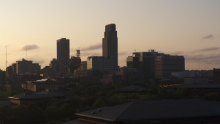 DX0002_172_012 - 5.7K stock footage aerial video approach and flyby skyscraper and skyline at sunset, Downtown Omaha, Nebraska