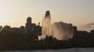 DX0002_172_015 - 5.7K stock footage aerial video focus on skyscraper while flying by fountain at sunset, Downtown Omaha, Nebraska