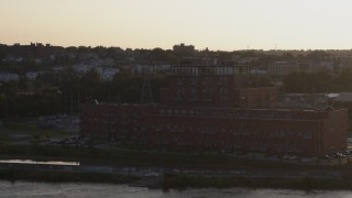 DX0002_172_017 - 5.7K stock footage aerial video orbit a riverfront apartment complex at sunset, Downtown Omaha, Nebraska