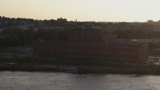DX0002_172_018 - 5.7K stock footage aerial video of circling and flying away from a riverfront apartment complex at sunset, Downtown Omaha, Nebraska