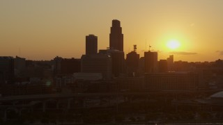 DX0002_172_023 - 5.7K stock footage aerial video orbit skyscraper and skyline with view of setting sun, Downtown Omaha, Nebraska