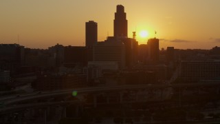 DX0002_172_026 - 5.7K stock footage aerial video slowly circle skyscraper and skyline with setting sun in background, Downtown Omaha, Nebraska
