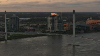 DX0002_172_028 - 5.7K stock footage aerial video orbit condo complex behind a pedestrian bridge spanning the Missouri River at sunset, Omaha, Nebraska