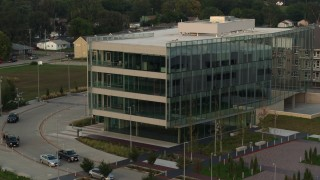 DX0002_172_035 - 5.7K stock footage aerial video of a reverse view of a modern office building at sunset in Council Bluffs, Iowa