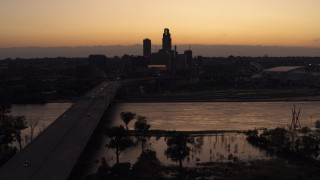 DX0002_172_043 - 5.7K stock footage aerial video flyby and approach the skyline and a bridge over the river at twilight, Downtown Omaha, Nebraska