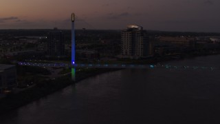 DX0002_172_049 - 5.7K stock footage aerial video orbit and fly away from a pedestrian bridge spanning the Missouri River at twilight, Omaha, Nebraska