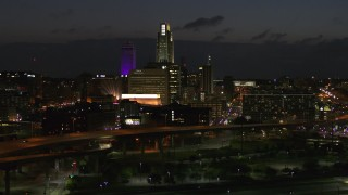 DX0002_173_019 - 5.7K stock footage aerial video fly away from the city's skyline at twilight, seen from river, Downtown Omaha, Nebraska
