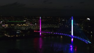 DX0002_173_022 - 5.7K stock footage aerial video of flying away from a pedestrian bridge spanning the Missouri River at night, Omaha, Nebraska