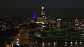 DX0002_173_035 - 5.7K stock footage aerial video follow bridge to approach the city's skyline at night, Downtown Omaha, Nebraska