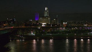 DX0002_173_036 - 5.7K stock footage aerial video fly over river to approach the city's skyline at night, Downtown Omaha, Nebraska