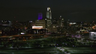 DX0002_173_037 - 5.7K stock footage aerial video fly away from city's skyline at night, reveal the river, Downtown Omaha, Nebraska