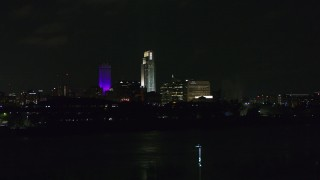 DX0002_173_038 - 5.7K stock footage aerial video ascend toward tall skyscrapers at night, Downtown Omaha, Nebraska