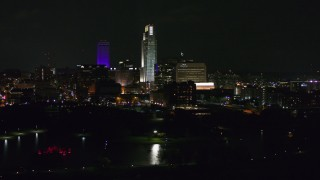 DX0002_173_040 - 5.7K stock footage aerial video of slowly passing tall skyscrapers at night, Downtown Omaha, Nebraska