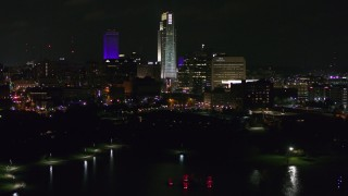 DX0002_173_048 - 5.7K stock footage aerial video of slowly ascending toward tall skyscrapers at night, Downtown Omaha, Nebraska