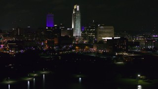 DX0002_173_049 - 5.7K stock footage aerial video of slowly flying away from tall skyscrapers at night, Downtown Omaha, Nebraska
