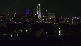 DX0002_173_050 - 5.7K stock footage aerial video of a reverse view of tall skyscrapers at night, Downtown Omaha, Nebraska