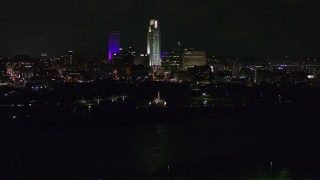 DX0002_173_051 - 5.7K stock footage aerial video of a reverse view of tall skyscrapers at night as the fountain lights up, Downtown Omaha, Nebraska