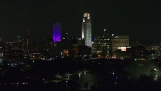 DX0002_173_058 - 5.7K stock footage aerial video ascend and flyby towering skyscrapers and high-rises at night, Downtown Omaha, Nebraska