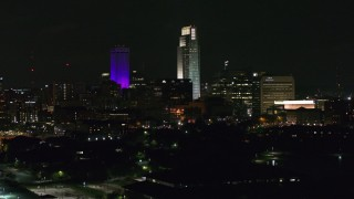 DX0002_173_059 - 5.7K stock footage aerial video towering skyscrapers seen from the park at night, Downtown Omaha, Nebraska