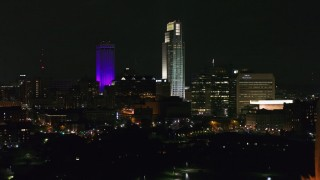 DX0002_173_063 - 5.7K stock footage aerial video fly away from city's skyscrapers, reveal the park fountain at night, Downtown Omaha, Nebraska
