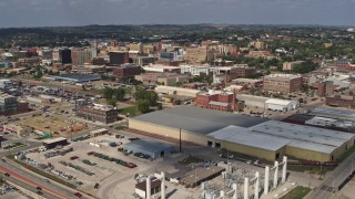 DX0002_174_009 - 5.7K stock footage aerial video flyby and away from warehouses with view of downtown, Sioux City, Iowa
