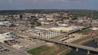 DX0002_174_010 - 5.7K stock footage aerial video reverse view of warehouses and downtown, seen from river, Sioux City, Iowa