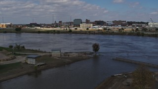 DX0002_174_021 - 5.7K stock footage aerial video fly low over river, ascend for view of Downtown Sioux City, Iowa