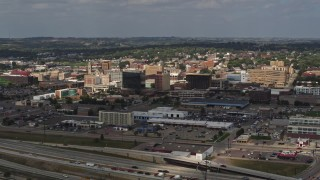 DX0002_174_030 - 5.7K stock footage aerial video reverse view of office buildings in Downtown Sioux City, Iowa, descend toward river