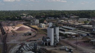 DX0002_175_032 - 5.7K stock footage aerial video orbit a train passing warehouse and industrial buildings in Sioux City, Iowa